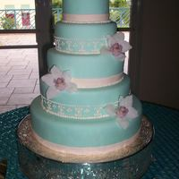Tiffany Tower Almond cake covered with homemade fondant. Fresh orchids and royal icing design. Thanks for looking!