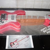 "Rickenbacker Bass Guitar Copied from a photo. On 28"" long board. Carved from 2 8"" Madeira cakes. Covered in fondant. All knobs and strings etc from..."