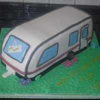 "Caravan Carved from a 10"" square, covered in fondant. All extras are fondant, Cake board covered then pressed with a star nozzle to get the..."