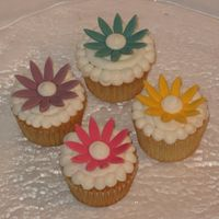 Flower Cupcakes White cake with BC frosting. We used the newer Wilton daisy cutouts. We made the flowers from fondant and dried them on upside-down egg...