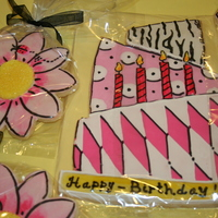 Birthday Cake Cookie And Flowers NFSC decorated with glace. The flowers were white, and I painted them with gel food color and vodka. All of the black on the cake and...