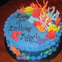 Coral Reef Cake Cake is covered in blue buttercream with gumpaste fish and coral. The crab is my favorite!