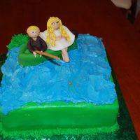 Bride And Groom Fishing Cake iced in buttercream.....fishing boat is made fomr rice crispy treats covered in fondant bride and groom are also fondant