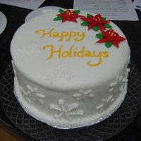 Poinsettia & Snowflakes Cake  Chocolate cake filled with cranberry buttercream, covered with MMF. Poinsettias and snowflakes on top of the cake are royal icing. The...