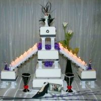 Square Formal Wedding Cake With Stairs Elegant 4-tier square wedding cake with stairs leading down to 2 satelite cakes adorned by black ribbons and purple African violets