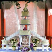 Emma's Simplicity Simple but elegant garden wedding cake featuring a fountain and white stairs. The cake boards are coved in purple florist paper to accent...