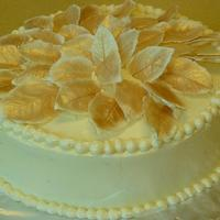 Cake For Potluck Inside is coconut cake; outside is Italian Buttercream, leaves are white chocolate dusted with Gold dust..