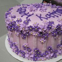 Kat's Purple Flowers Cake The cake is frosted with buttercream and decorated with royal icing drop flowers.