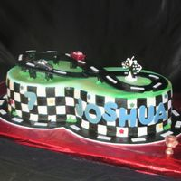 Joshua 7  Birthday cake for a good friend's seven year old son. Cake is covered in marshmallow fondant, letters and tracks are fondant. The...
