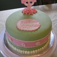 Mk Baptism 8in round covered in MFF with fondant and buttercream accents, and gumpaste flowers and cross. The fondant ribbon in the center of the cake...