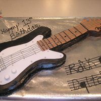 Guitar  I made this for my BILs birthday. guitar carved out of 9x13 pan, neck and top carved out of RKT. Iced in chocolate buttercream with fondant...