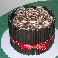 Strawberry Cake  This is a vanilla cake with a brownie filling. It is iced in vanilla buttercream, surrounded by Oreo Fun Stix, and topped with chocolate...