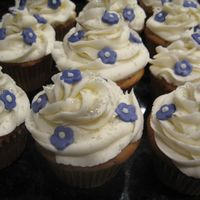 Flower Cupcakes Cupcakes iced in buttercream with purple fondant flowers and edible glitter.