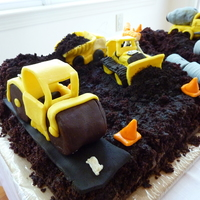 Construction Site Chocolate cake with white chocolate construction vehicles covered with chocolate clay. Road roller compacting a road at one end, while a...