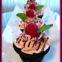 Chocolate Raspberry Cupcakes   Chocolate cupcakes filled with raspberry preserves, topped with raspberry SMBC.