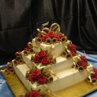 Golden Anniversary Iced in buttercream, with buttercream roses and sugar bells. Was asked to come up with a design for a customer using Red and Gold. This is...