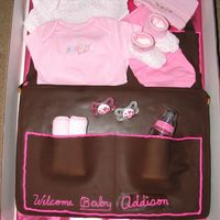 Diaper Bag Sheet cake covered with chocolate Fondant.All baby items are real so mom could keep.