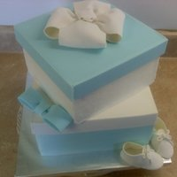 Package Babyshower Cake Stacked cakes with 5 panel box lids. Bottom of cakes iced smooth in buttercream. Gum paste bows and baby shoes. TFL