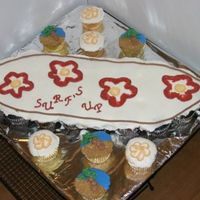 Luau Cupcakes  Surfboard cupcake cake , with palm trees and flowers on extra cupcakes. The sand is crushed graham crackers. Palm tree and flowers inspired...