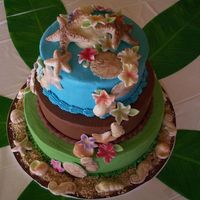 Seashell And Flowers Cascade Three tier cake (middle tier is chocolate, top and bottom are almond flavored) with a cascade of white chocolate seashells and bright...