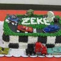 Disney Cars Birthday Cake 2 layer 13x9 inch cake iced with BC, fondant race track and real toy cars.