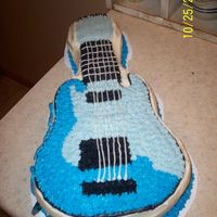 Electric Guitar Wilton Pan, all ButterCream Dream. I wrote the guys name on the side (turned out bad) and stuck a real blue guitar pick next to it. Would...