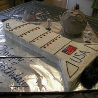 "Space Cake Half Sheet cake cut to make the space shuttle. Ran out of frosting, so only a ""crumb coat"" is on the shuttle. Would have looked..."