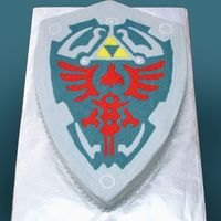 Hylian Shield From Legend Of Zelda Chocolate cake with buttercream icing. I piped the whole top in zigzag patterns and then smoothed it out with a viva paper towel.