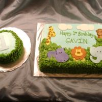 Safari Animals A first birthday cake with safari animals. I drew the animals and cut them out of fondant. The leaves and grass are buttercream.