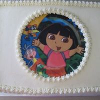 Dora 9x13 yellow cake with cream cheese frosting and an edible image of Dora made from the party plates.