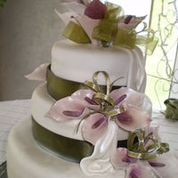 Calla Lillibration Three-tiered fruit cake with waterfall drapes and lilly sprays accented by green banding.