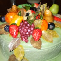 Nature's Bounty Fruits and vegetables modelled from marzipan and complement with fondant leaves adorn this fruitcake covered with green fondant icing.
