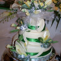 Calla Lillies And Roses Burst Calla lilles and roses done in the bridal theme colours of cream, pale yellow and green. Covered in cream fondant with drapes and green...
