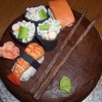 Sushi Cake Modelled Sushi on a chocolate ganache covered cake.