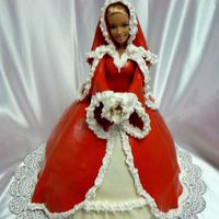 "Christmas Barbie Red Velvet in Wonder Mols with 8"" yellow cake as base, covered in MMF with RI ""fur""."