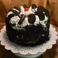 Cookies & Cream Devil's Food Cake with Chocolate cream filling, Whipped Topping icing with Oreo cookie crumbs on side & decorated with Oreos,...