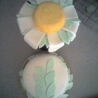 Daisy Cake Red velvet cake w/ cream cheese filling. Fondant icing on the cake, the leaves and daisy petals. Large sugar cookie for the yellow portion...
