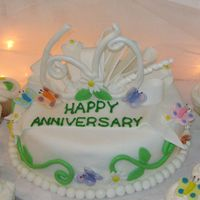 60Th Wedding Anniversary Vanilla cake with buttercrem icing. Cake is covered in fondant. Butterflies and flowers are also fondant. Also made matching cup cakes. The...