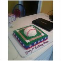 Baseball square cake with 1/2 ball pan baseball on top. little painted fondant baseballs on side, graham cracker crumb field