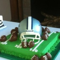 "Dallas Cowboys Helmet 12"" square cake as football field. Helmet is two 6"" rounds and half the ball pan and was then sculpted. Face mask is gum paste..."