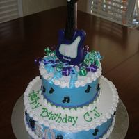 Electric Guiter Cake   Two tier banana cake iced in buttercream. Molded chocolate electric guitar anf music notes.