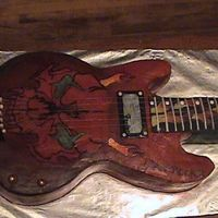 Guitar A 28 INCH GUITAR CAKE WITH SKULL AND FLAMES THAT TRAVEL.