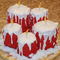 "Christmas Candles This group of Christmas candles was decorated with buttercream and white chocolate, with fondant flames. The ""snow"" around the..."