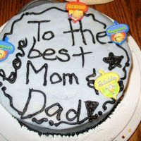 Practice Cake For Mom And Dad A white cake with chocolate filling covered with purple frosting and piped black writing. Plastic decorative rings. A practice cake.
