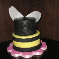 Bee Cake  A 2 tier cake decorated in fondant to resemble a bee. The board is decorated to resemble a flower. Wings are rice paper, antennae are...