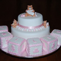 Emila's Christening Cake Top tier is caramel mudcake with white fondant icing and bottom tier is chocolate mudcake with fondant icing, blocks are foam which have...