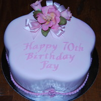 70Th Birthday Cake This is a white choc mud cake covered in marbled pink fondant. Camilla and roses are made from flower paste.