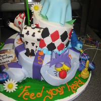 Alice In Wonderland  3 tiered cake with accents of Alice in Wonderland on all layers with Alice stuck in the cake and tea party on top layered with mushrooms,...