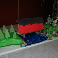 3D Wedding Cake  Bride wanted a covered bridge made out of ginger bread with cakes on each side carved into landscaping along with rocks, water, cat tails,...
