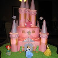Disney Princesses Castle Cake Two tier chocolate cake covered with foundant. Towers are made by ice-cream cones covered in foundant.